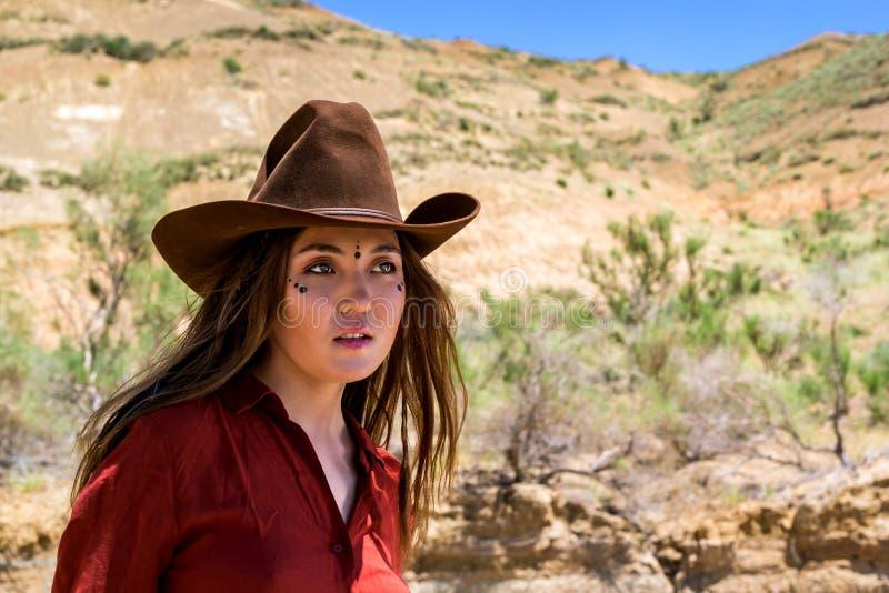 Κορίτσι σε ένα καπέλο κάουμποϋ σε ένα υπόβαθρο των βουνών στοκ φωτογραφία
