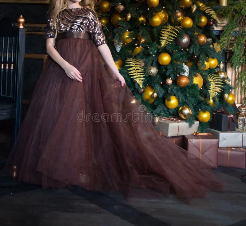 Κορίτσι σε ένα καφετί φόρεμα κοντά στο χριστουγεννιάτικο δέντρο Χριστουγεννιάτικο δέντρο με τις κίτρινες σφαίρες, τα κεριά και τη στοκ εικόνα με δικαίωμα ελεύθερης χρήσης