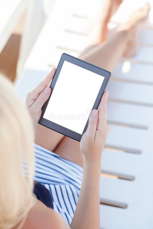 Κορίτσι σε ένα κοστούμι λουσίματος που βρίσκεται σε ένα σαλόνι μονίππων με έναν υπολογιστή στοκ φωτογραφία