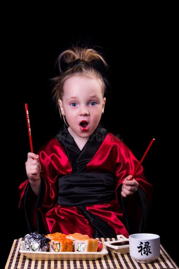 Κορίτσι σε ένα κόκκινο κιμονό πριν από ένα πιάτο με τους ρόλους στοκ φωτογραφία με δικαίωμα ελεύθερης χρήσης