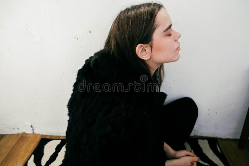 Κορίτσι σε ένα μαύρο παλτό ενάντια σε έναν άσπρο τοίχο στοκ φωτογραφία με δικαίωμα ελεύθερης χρήσης