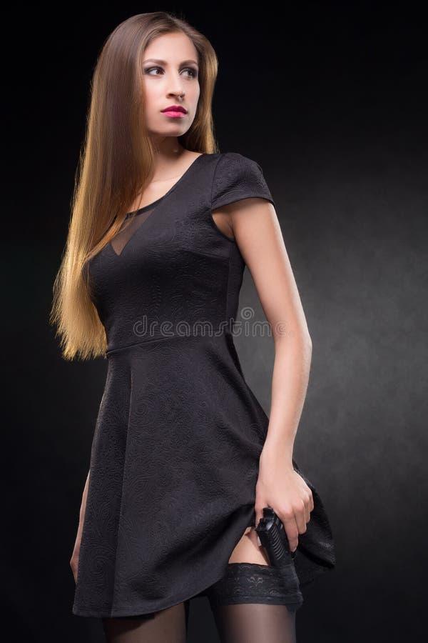 Κορίτσι σε ένα μαύρο φόρεμα που κρατά ένα πυροβόλο όπλο στοκ εικόνα με δικαίωμα ελεύθερης χρήσης