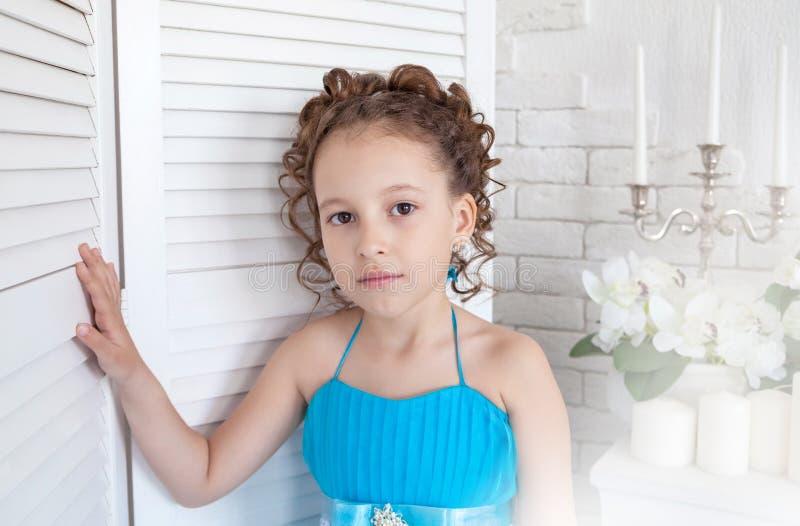 Κορίτσι σε ένα μπλε φόρεμα δίπλα σε μια οθόνη στοκ εικόνα με δικαίωμα ελεύθερης χρήσης
