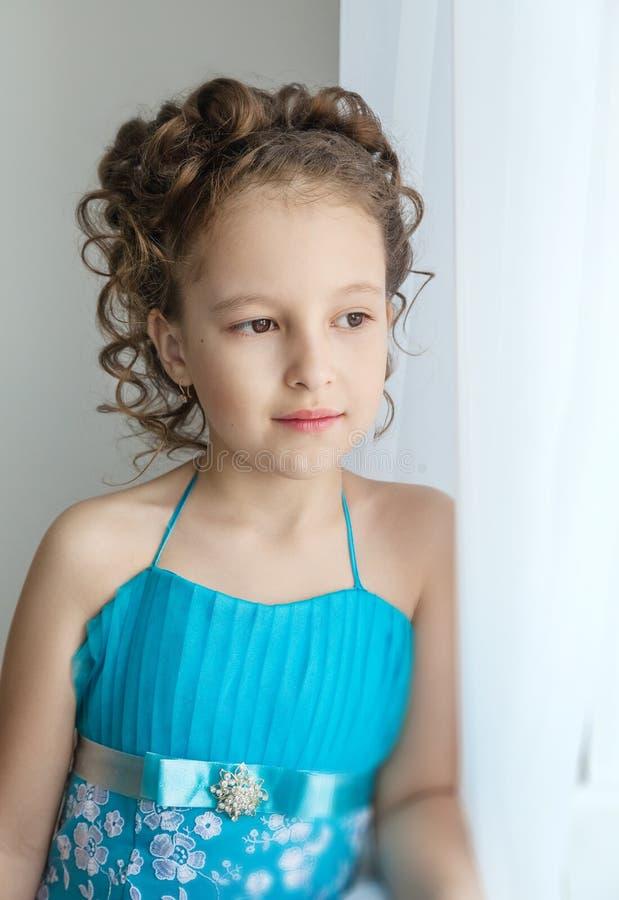 Κορίτσι σε ένα μπλε φόρεμα και να φανεί έξω το παράθυρο στοκ φωτογραφία με δικαίωμα ελεύθερης χρήσης