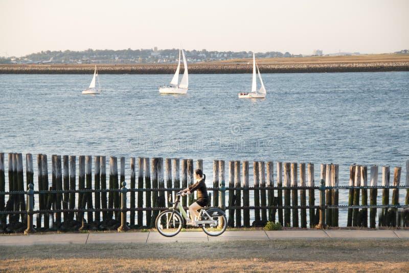 Κορίτσι σε ένα ποδήλατο που οδηγά μετά από το λιμάνι της Βοστώνης, Βοστώνη, Μασαχουσέτη στοκ φωτογραφία με δικαίωμα ελεύθερης χρήσης