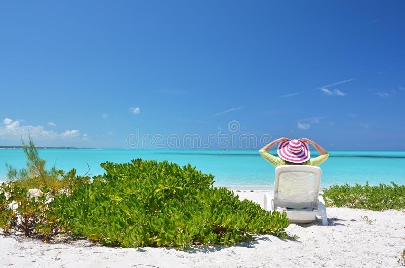Κορίτσι σε ένα ριγωτό καπέλο στην παραλία στοκ εικόνες