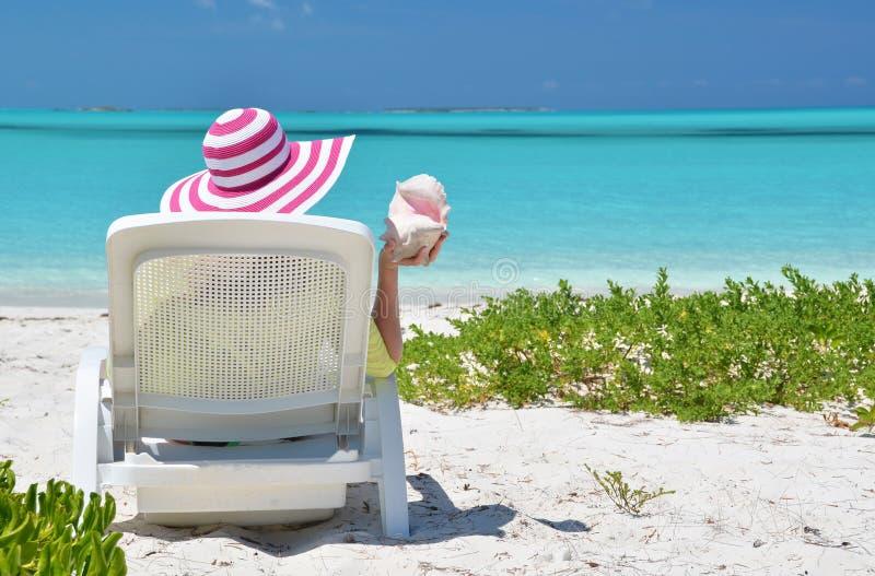 Κορίτσι σε ένα ριγωτό καπέλο στην παραλία στοκ φωτογραφίες