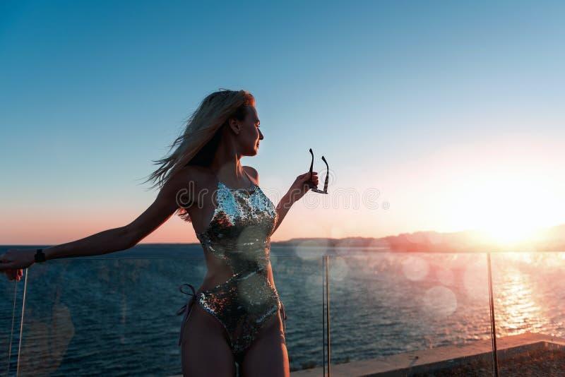 Κορίτσι σε ένα όμορφο κοστούμι λουσίματος στο ηλιοβασίλεμα από τα γυαλιά ηλίου εκμετάλλευσης θάλασσας στοκ εικόνα με δικαίωμα ελεύθερης χρήσης