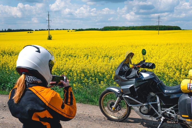 Κορίτσι σε μια εξάρτηση προστασίας και γυαλιά με την τουριστική μοτοσικλέτα κίτρινος τομέας λουλουδιών Γύρος ιχνών περιπέτειας, e στοκ εικόνες
