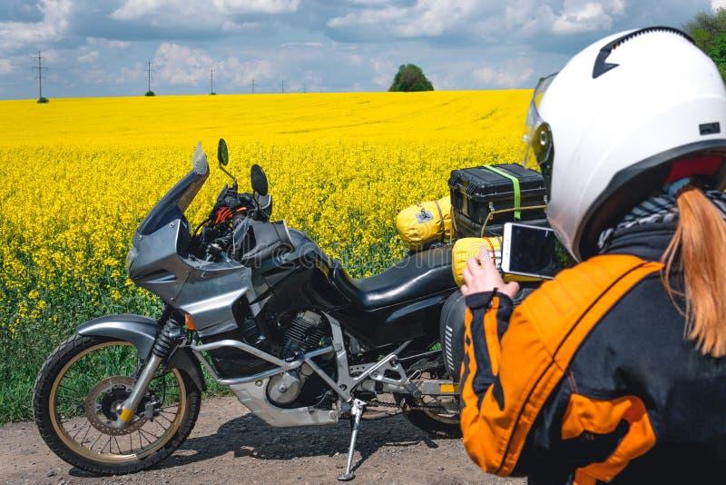 Κορίτσι σε μια εξάρτηση προστασίας και γυαλιά με την τουριστική μοτοσικλέτα κίτρινος τομέας λουλουδιών Γύρος ιχνών περιπέτειας, e στοκ φωτογραφίες με δικαίωμα ελεύθερης χρήσης