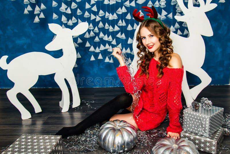 Download Κορίτσι σε μια κόκκινη συνεδρίαση πουλόβερ με τα δώρα Χριστουγέννων Νέο έτος Con Στοκ Εικόνες - εικόνα από γιρλάντες, βακκινίων: 62704894
