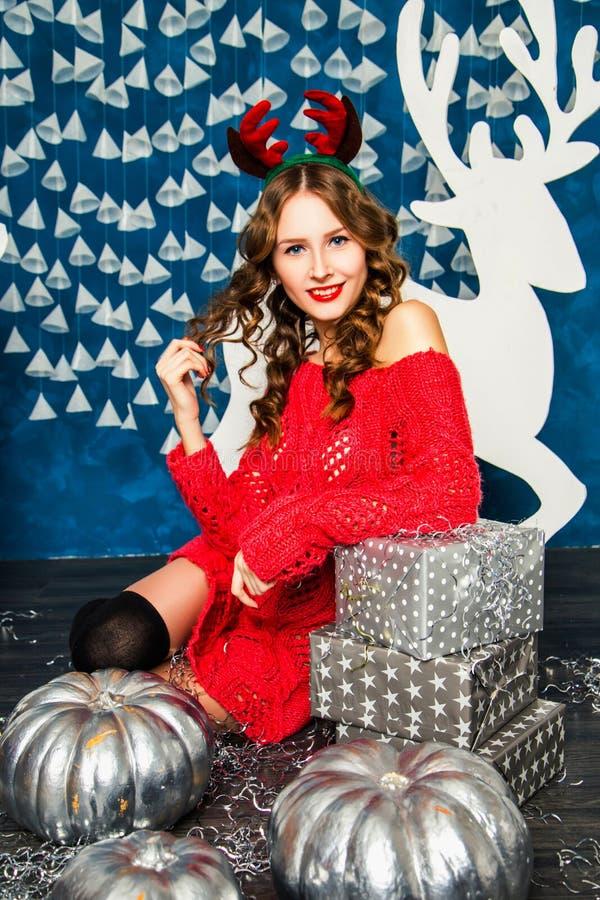 Download Κορίτσι σε μια κόκκινη συνεδρίαση πουλόβερ με τα δώρα Χριστουγέννων Νέο έτος Con Στοκ Εικόνες - εικόνα από χριστούγεννα, πουλόβερ: 62704972