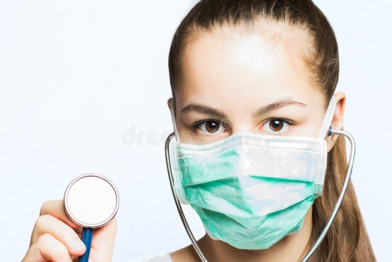 Κορίτσι σε μια μάσκα γιατρών που κρατά ένα στηθοσκόπιο - ιατρική έννοια στοκ εικόνες με δικαίωμα ελεύθερης χρήσης