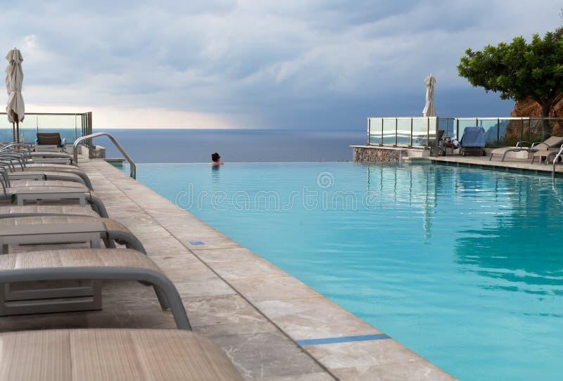 Κορίτσι σε μια πισίνα με τις απόψεις θάλασσας στοκ εικόνα