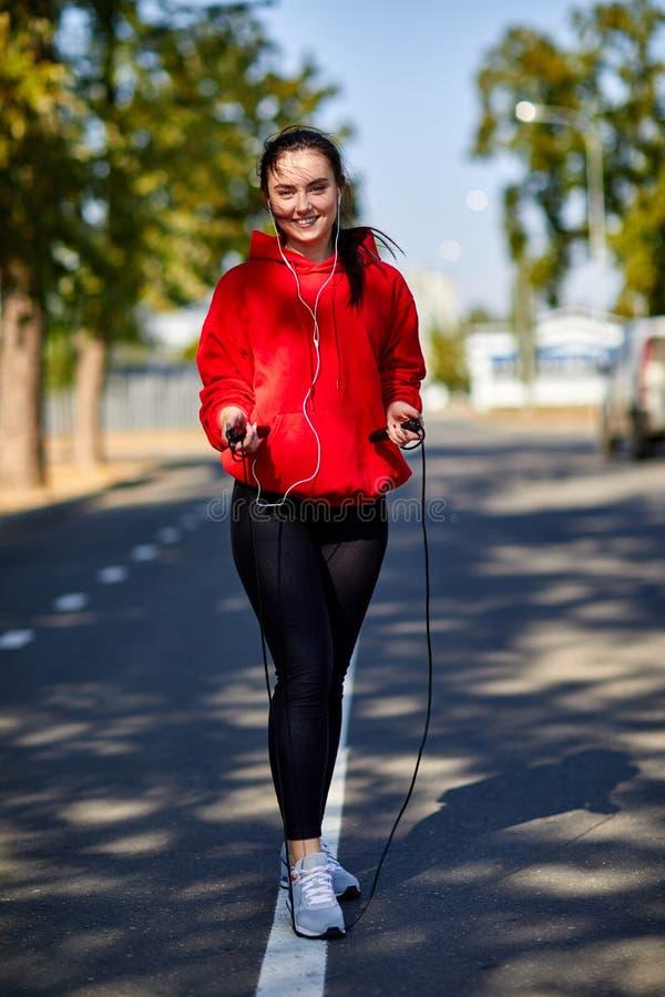 Κορίτσι σε μια προθέρμανση στο πάρκο με ένα πηδώντας σχοινί στοκ φωτογραφίες με δικαίωμα ελεύθερης χρήσης