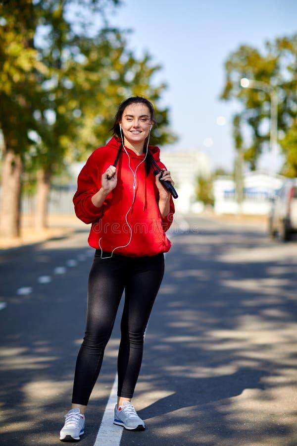 Κορίτσι σε μια προθέρμανση στο πάρκο με ένα πηδώντας σχοινί στοκ εικόνα