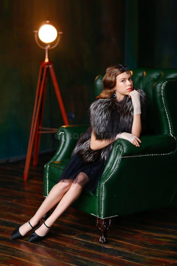 Κορίτσι σε μια συνεδρίαση gatsby-ύφους σε μια πολυτελή πολυθρόνα στα γάντια στοκ εικόνα