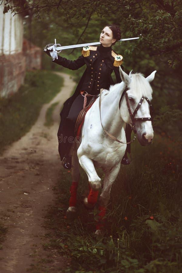 Κορίτσι σε ομοιόμορφο με το ξίφος στον ώμο της που οδηγά το άσπρο άλογο στοκ εικόνες