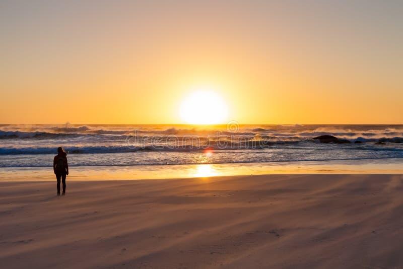 Κορίτσι σκιαγραφιών που προσέχει ένα ηλιοβασίλεμα σε μια αμμώδη παραλία με την τραχιά Oc στοκ εικόνα
