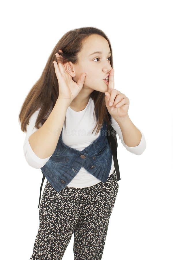 Κορίτσι σπουδαστών με το δάχτυλο στο στόμα, να κρυφακούσει στοκ εικόνες