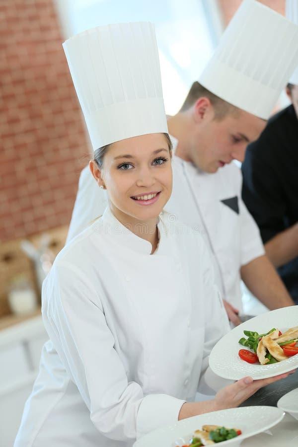 Κορίτσι σπουδαστών μεταξύ της ομάδας μαγειρεύοντας μαθητευόμενων στοκ εικόνες με δικαίωμα ελεύθερης χρήσης