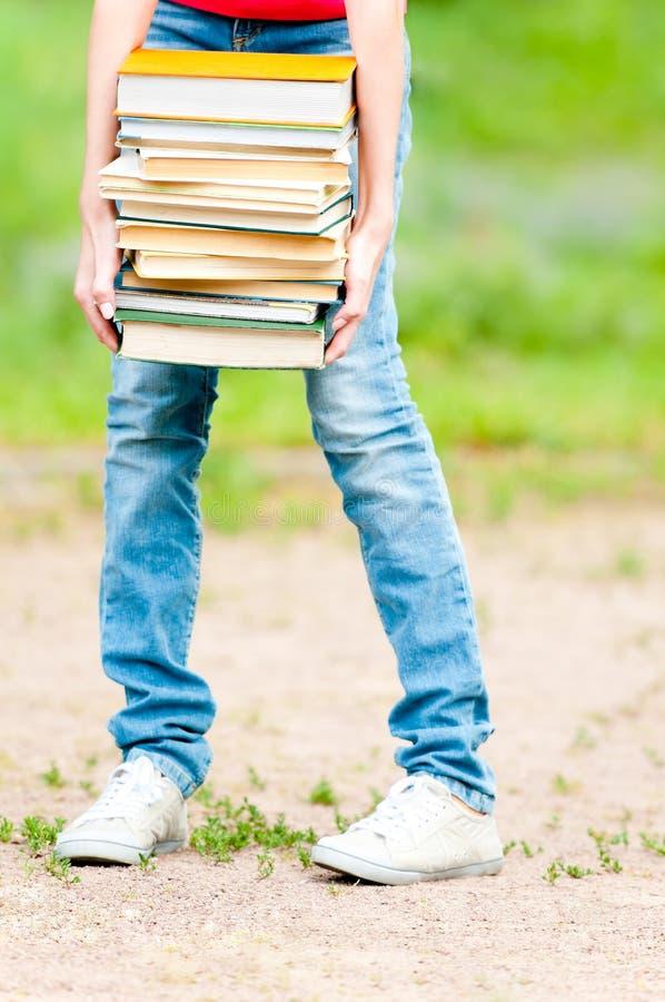 Κορίτσι σπουδαστών που κρατά το μεγάλο σωρό των βαριών βιβλίων στοκ εικόνες με δικαίωμα ελεύθερης χρήσης