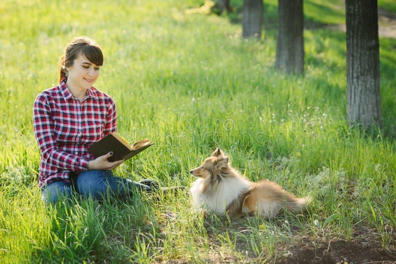 Κορίτσι σπουδαστών που μαθαίνει στη φύση με το σκυλί στοκ φωτογραφίες