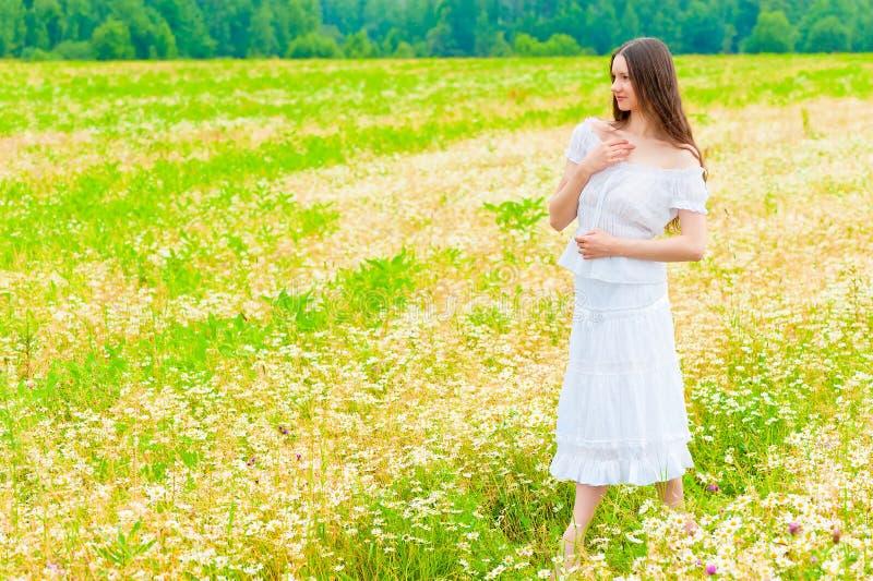 Κορίτσι στα άσπρα sundress που περπατά στο chamomile τομέα στοκ φωτογραφίες