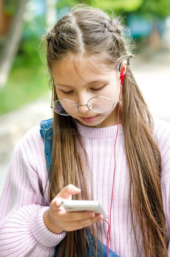 Κορίτσι στα γυαλιά με ένα τηλέφωνο στα χέρια τους στοκ εικόνες με δικαίωμα ελεύθερης χρήσης