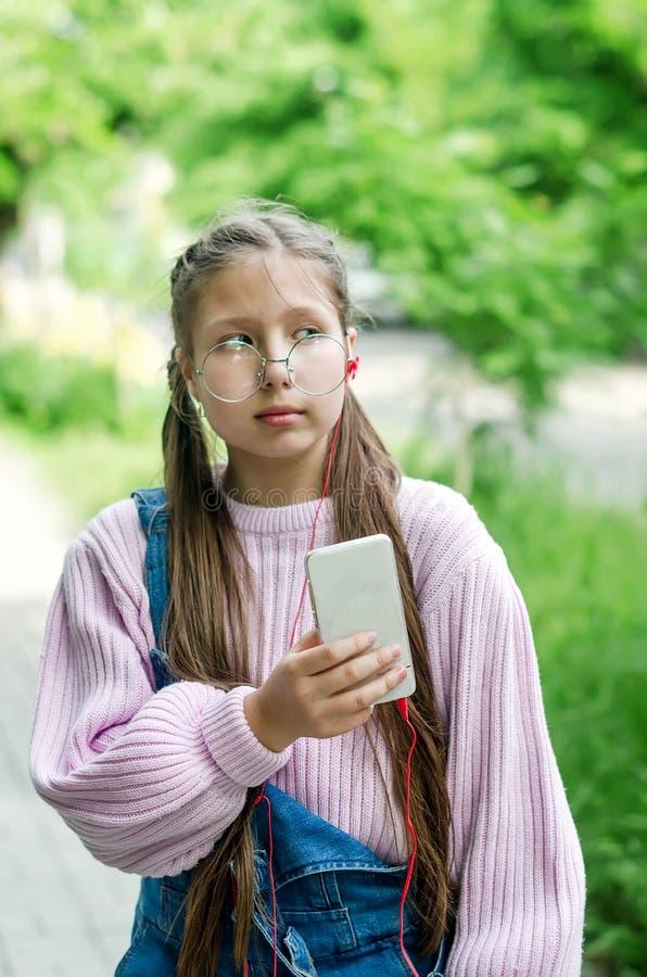 Κορίτσι στα γυαλιά με ένα τηλέφωνο στα χέρια τους στοκ εικόνες