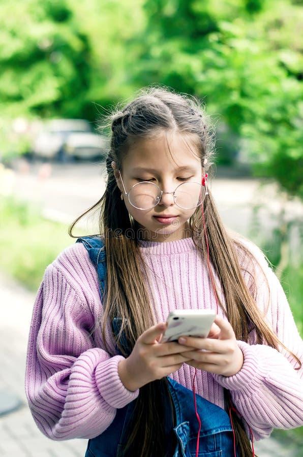 Κορίτσι στα γυαλιά με ένα τηλέφωνο στα χέρια τους στοκ φωτογραφία με δικαίωμα ελεύθερης χρήσης