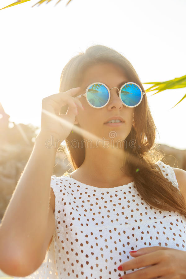 Κορίτσι στα γυαλιά ηλίου κατά τη διάρκεια του ηλιοβασιλέματος στοκ φωτογραφία