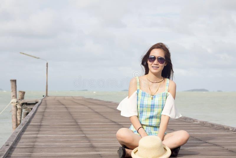 Κορίτσι στα γυαλιά ηλίου στο ξύλινο υπόβαθρο γεφυρών και θάλασσας στοκ φωτογραφίες