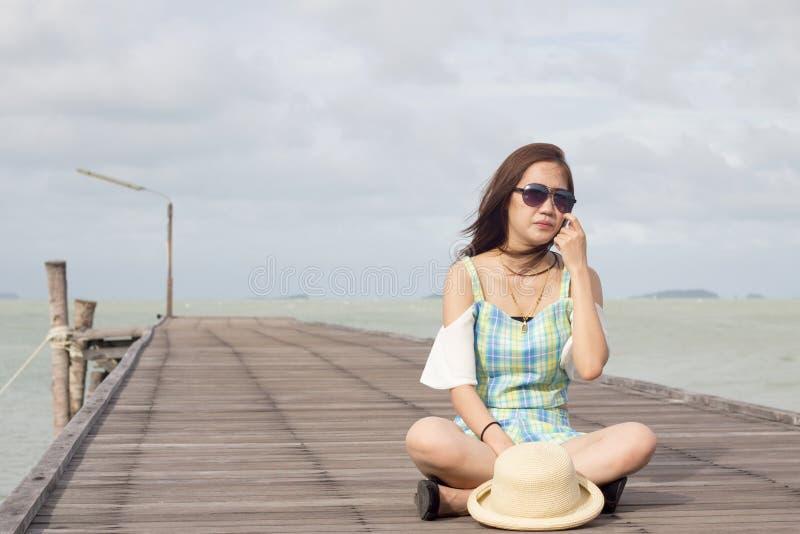 Κορίτσι στα γυαλιά ηλίου στο ξύλινο υπόβαθρο γεφυρών και θάλασσας στοκ φωτογραφία