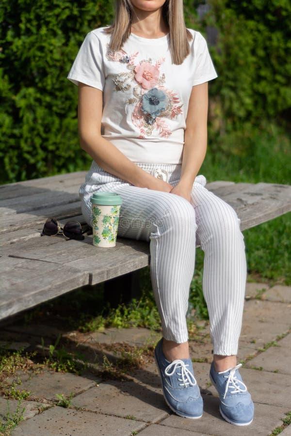 Κορίτσι στα ριγωτά εσώρουχα και τα μπλε παπούτσια που κάθεται σε έναν ξύλινο πάγκο δίπλα σε ένα φλιτζάνι του καφέ και τα γυαλιά η στοκ εικόνες