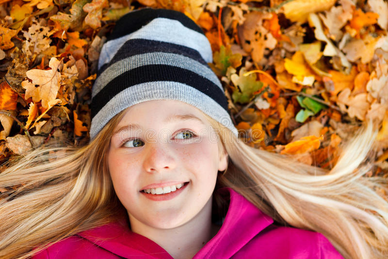 Κορίτσι στα φύλλα φθινοπώρου που χαμογελούν και που κοιτάζουν λοξά στοκ φωτογραφίες με δικαίωμα ελεύθερης χρήσης