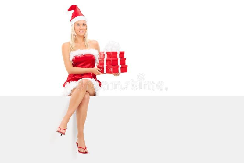 Κορίτσι στα δώρα εκμετάλλευσης κοστουμιών santa που κάθονται στην επιτροπή στοκ εικόνες με δικαίωμα ελεύθερης χρήσης