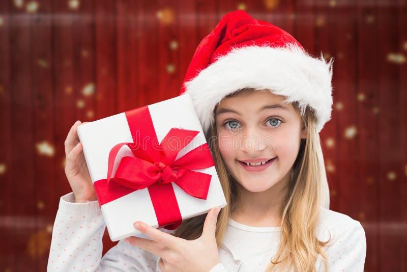 Κορίτσι στα δώρα Χριστουγέννων εκμετάλλευσης καπέλων santa στοκ φωτογραφία με δικαίωμα ελεύθερης χρήσης
