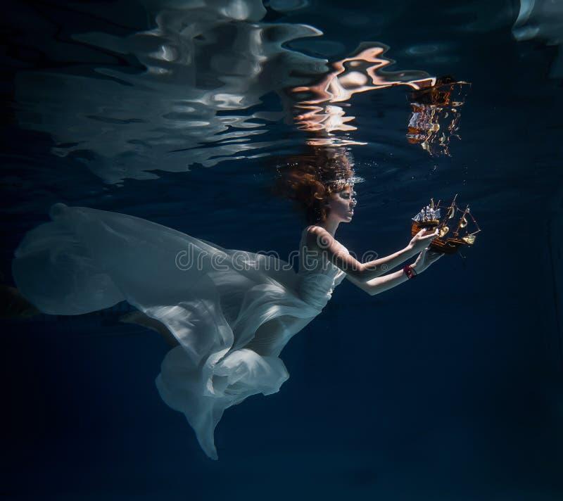 Κορίτσι στην άσπρη τοποθέτηση φορεμάτων κάτω από το νερό με τη βάρκα στοκ φωτογραφίες