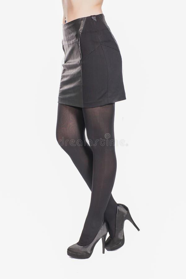 Κορίτσι στην απότομα μαύρη φούστα και τα υψηλά τακούνια Θηλυκά πόδια κινηματογραφήσεων σε πρώτο πλάνο στοκ εικόνες