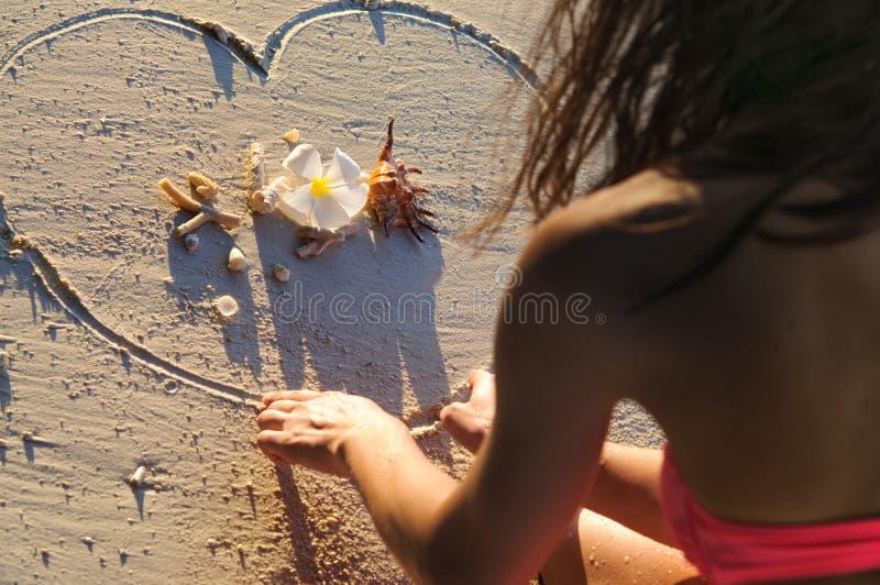Κορίτσι στην καρδιά σχεδίων παραλιών στην άμμο στοκ εικόνα