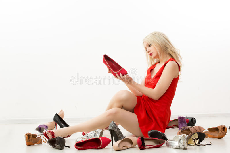 Κορίτσι στην κόκκινη συνεδρίαση φορεμάτων στο πάτωμα επιλέγει στοκ φωτογραφίες με δικαίωμα ελεύθερης χρήσης