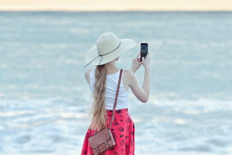 Κορίτσι στην κόκκινη φούστα και καπέλο που κάνει selfie στην παραλία στη θάλασσα και στοκ φωτογραφίες