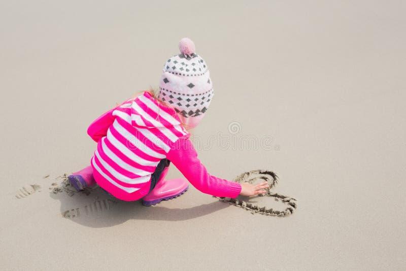 Κορίτσι στη θερμή μορφή καρδιών σχεδίων ιματισμού στην άμμο στην παραλία στοκ εικόνες