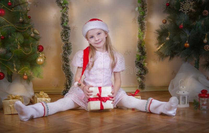 Κορίτσι στη συνεδρίαση καπέλων Santa με το δώρο μεταξύ του χριστουγεννιάτικου δέντρου στοκ εικόνες