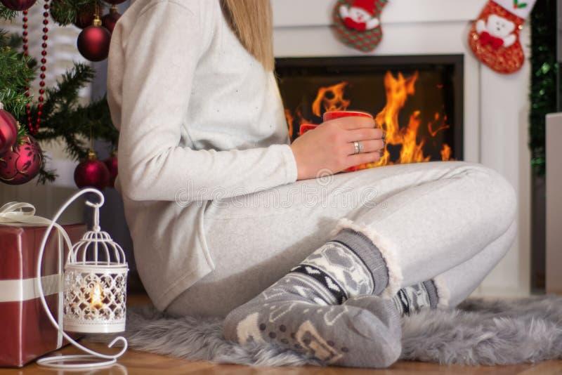 Κορίτσι στις κάλτσες και τις πυτζάμες Χριστουγέννων που κάθεται κοντά στην εστία στοκ φωτογραφίες