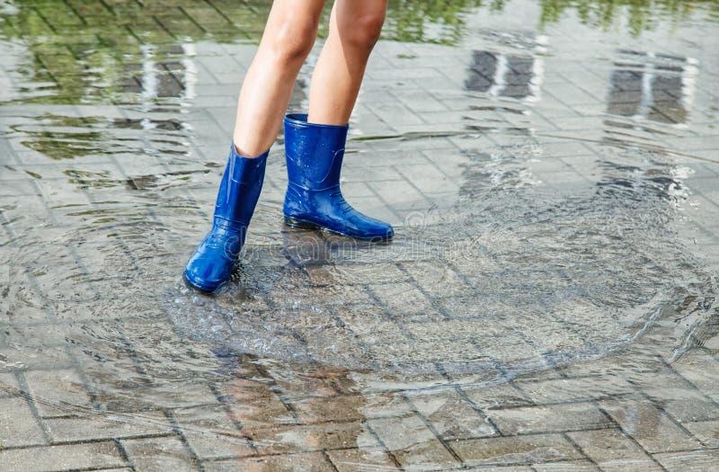 Κορίτσι στις λαστιχένιες μπότες που στέκονται σε μια λακκούβα μετά από μια βροχή στοκ εικόνες