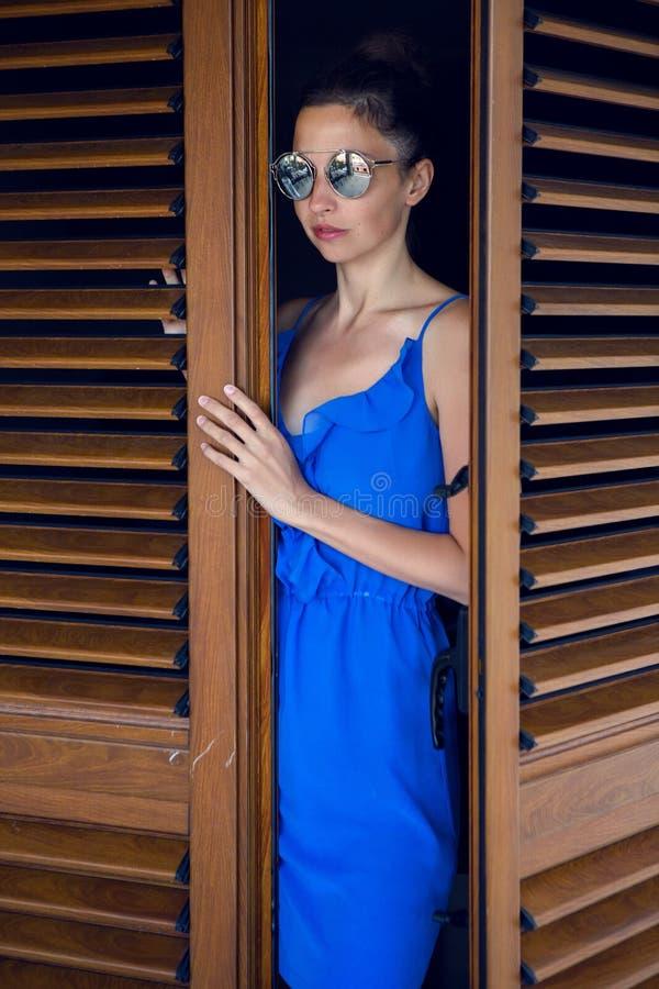 Κορίτσι στις μπλε στάσεις φορεμάτων στην πόρτα στοκ εικόνες
