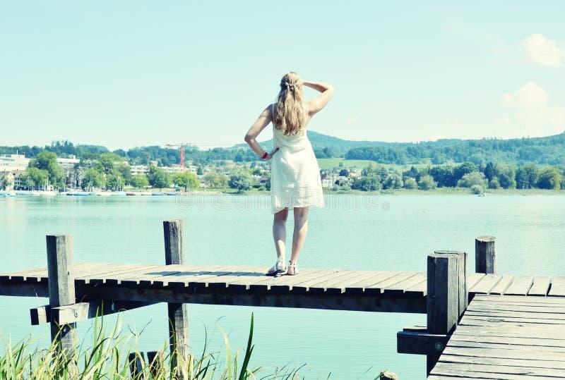 Κορίτσι στον ξύλινο λιμενοβραχίονα στοκ φωτογραφία με δικαίωμα ελεύθερης χρήσης