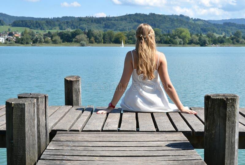 Κορίτσι στον ξύλινο λιμενοβραχίονα στοκ εικόνα